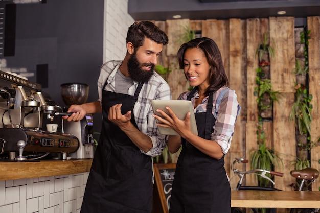 Официант и официантки, используя ноутбук во время работы