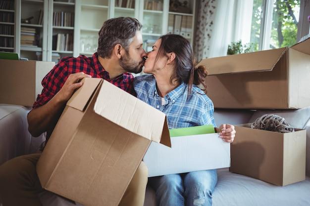 Молодая пара целует друг друга, распаковывая картонные коробки