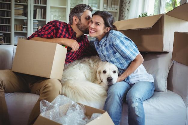 Мужчина целует женщину во время распаковки картонных коробок
