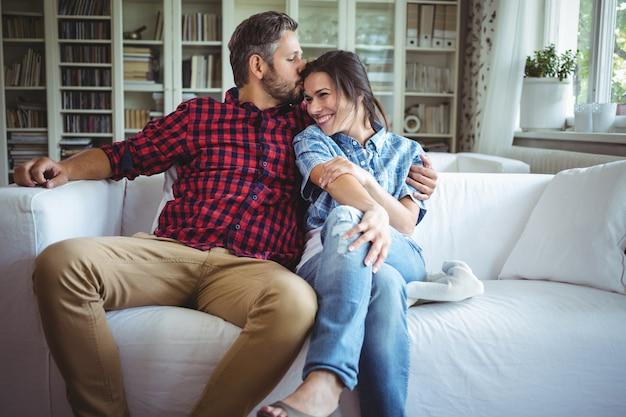 Мужчина целует женщину сидя на диване в гостиной