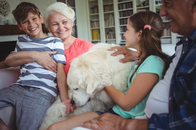 Бабушка и дедушка и внуки сидят на диване с собакой