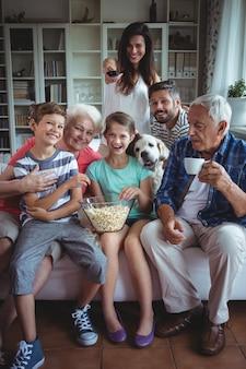 Счастливая семья смотрит футбольный матч по телевизору в гостиной