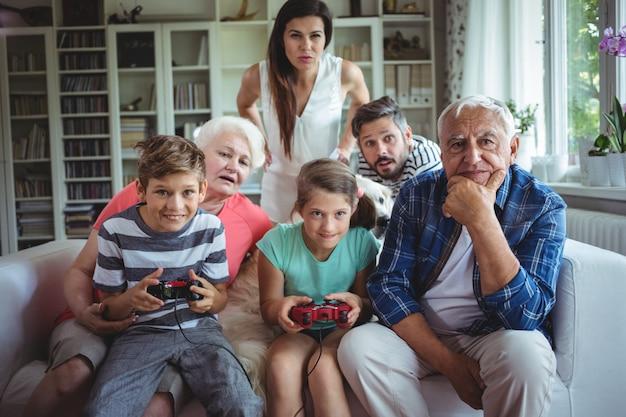 Семья смотрит на детей, играющих в видеоигры
