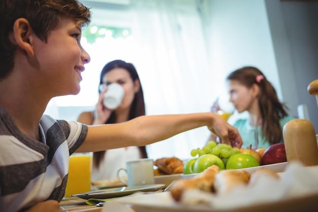 朝食をとりながらトレイから果物を拾う少年