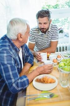 朝食をとりながらお互いに話している父と息子