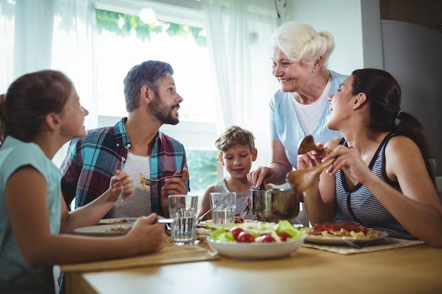 Пожилая женщина подает еду своей семье