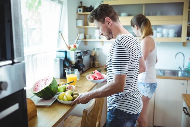 Пара готовит завтрак с фруктами