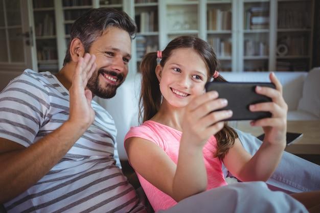 リビングルームで携帯電話を見て笑顔の父と娘