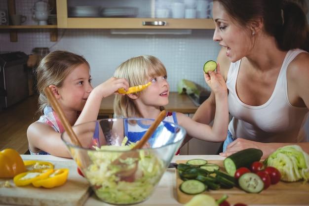 キッチンで母親にズッキーニのスライスを食べさせる子供たち