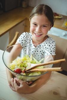 Девушка держит миску салата на кухне