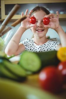 Игривая девушка держит помидор черри на глаз