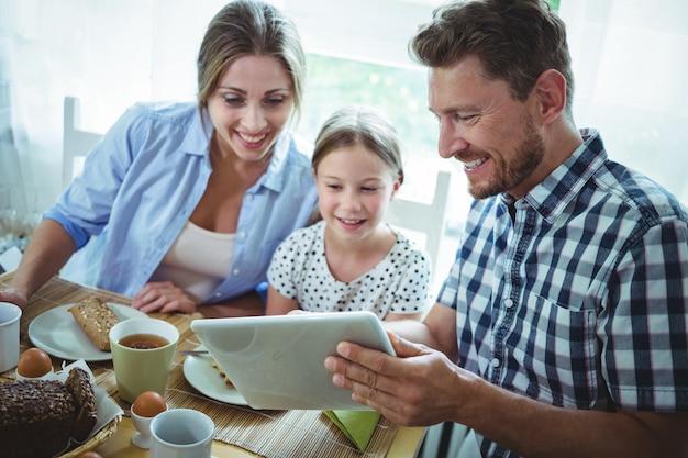 朝食をとりながらデジタルタブレットを使用して家族