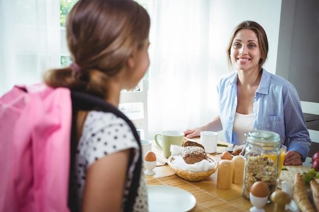 Мать общается с дочерью во время завтрака