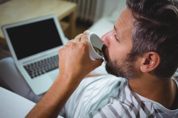 Человек, имеющий кофе при использовании ноутбука