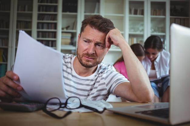 彼の妻と娘がソファに座っている間に法案を計算する心配の男