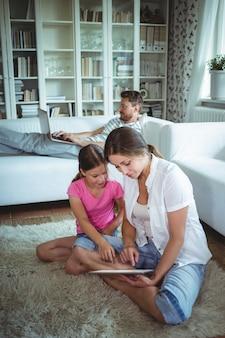 Мать и дочь, сидя на полу и с помощью цифрового планшета