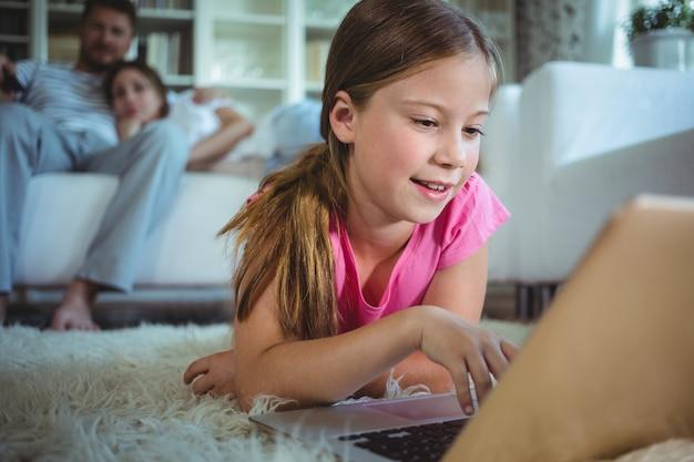 Девушка лежит на полу и использует ноутбук