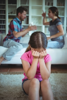両親がリビングルームで主張しながら泣いている悲しい少女