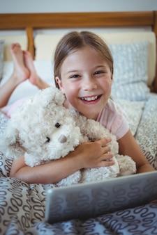 Счастливая девушка, лежа на кровати с мишкой и с помощью цифрового планшета