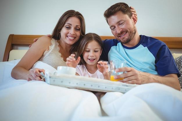 娘と一緒にベッドに座って朝食をとる親