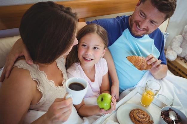 Родители сидят на кровати с дочерью и завтракают