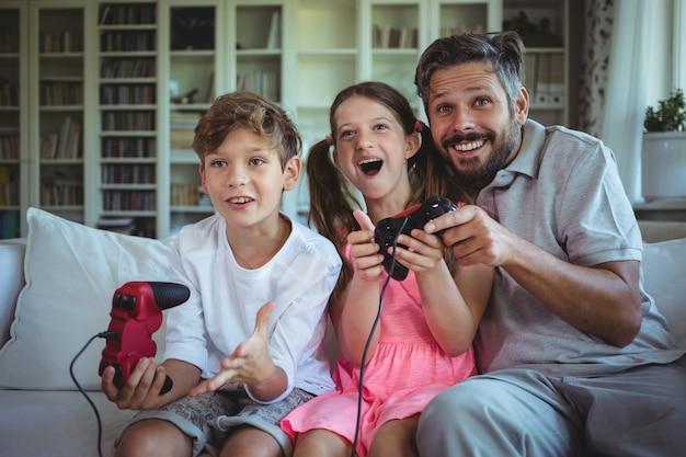 Отец сидит на диване со своими детьми и играет в видеоигры