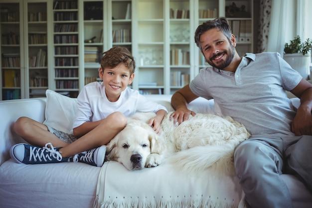 父と息子のリビングルームで愛犬とソファに座って
