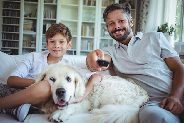 父と息子の愛犬とソファに座ってテレビを見て