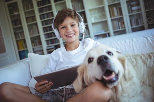 ペットの犬とソファの上に座って、デジタルタブレットで音楽を聴く少年