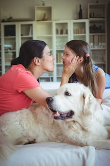 Мать и дочь сидят с собакой в гостиной