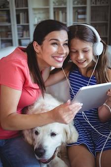 Счастливая мать и дочь, сидя с собакой и слушать музыку в наушниках