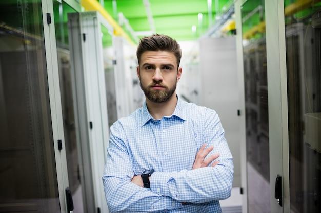 Техник, стоя со скрещенными руками в серверной комнате
