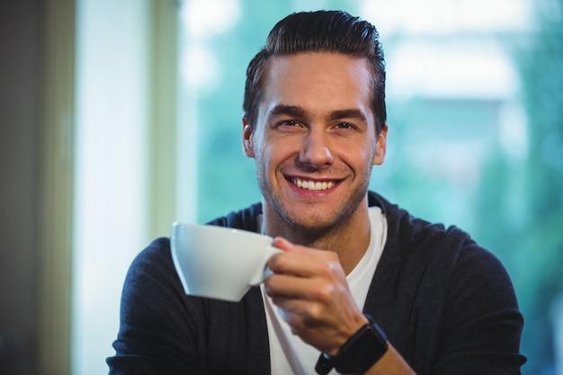 カフェでコーヒーを飲んでいるハンサムな男