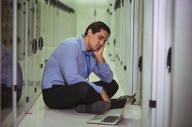 床に座ってノートパソコンを見て技術者を強調