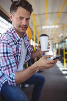 Портрет красивого человека используя мобильный телефон пока имеющ кофе