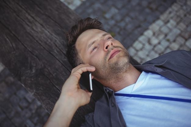 携帯電話で話しているハンサムなビジネスエグゼクティブ