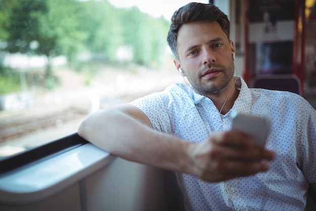 Красивый мужчина слушает музыку на мобильном телефоне