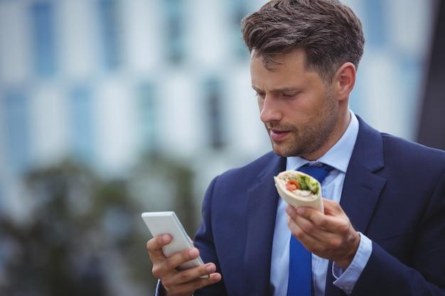 携帯電話を使用してハンサムな実業家