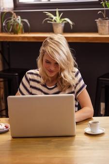 女性は机の上に座ってラップトップを使用して