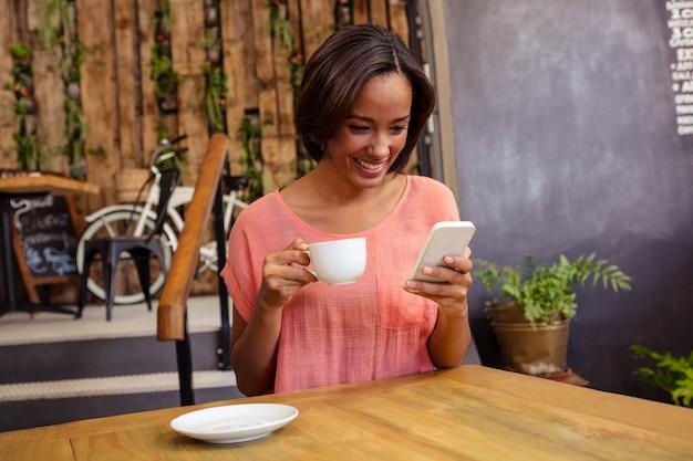 Женщина пьет кофе и с помощью смартфона