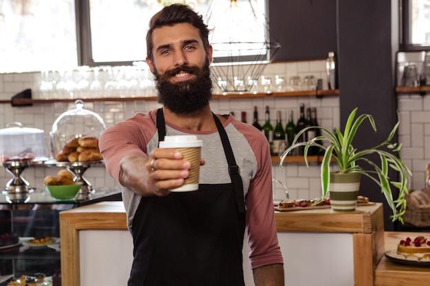 Официант, представляя одноразовую чашку