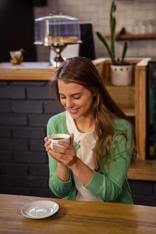 一杯のコーヒーを保持している女性の笑みを浮かべてください。
