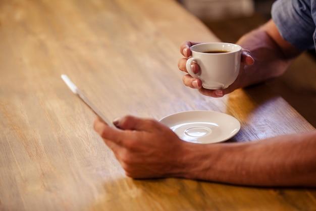 一杯のコーヒーを飲みながらスマートフォンを使用して流行に敏感な男の画像をトリミング