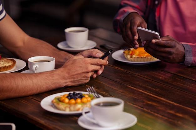 Обрезанное изображение друзей, едящих выпечку и пьющих кофе