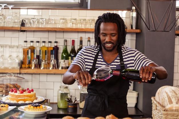 笑顔のヒップスター従業員がワインのグラスを充填