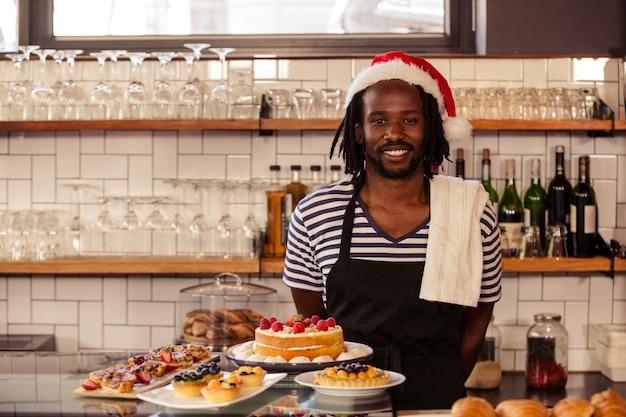 Счастливый работник битник позирует с рождеством шляпу