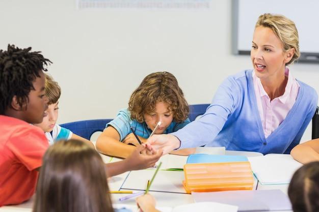 Учитель помогает школьнице с ее домашней работой в классе