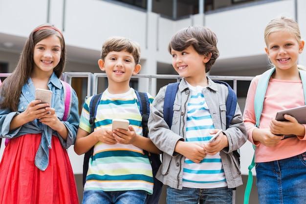 学校のテラスに立っている携帯電話とデジタルタブレットを保持している子供