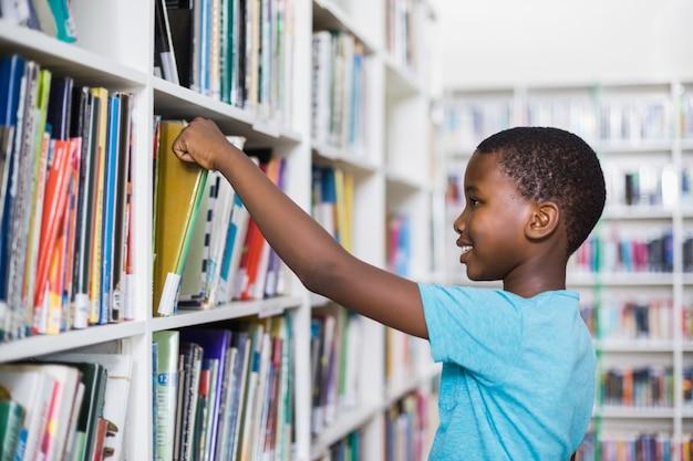 図書館の本棚から本を選択する少年
