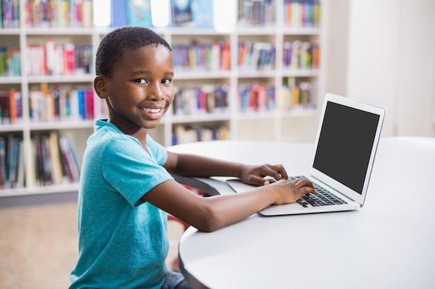 図書館でラップトップを使用して少年